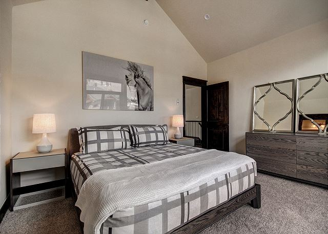 The first master bedroom features a king-sized bed, a mounted flat screen TV and its own private deck.
