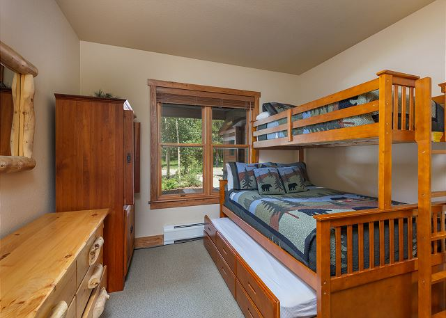 The guest bedroom features a twin-over-queen bunk bed with a twin trundle that pulls out from underneath.