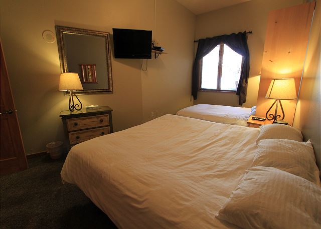 The bedroom features a king-sized bed and a queen-sized Murphy bed, both on the Ivory White Bedding program.