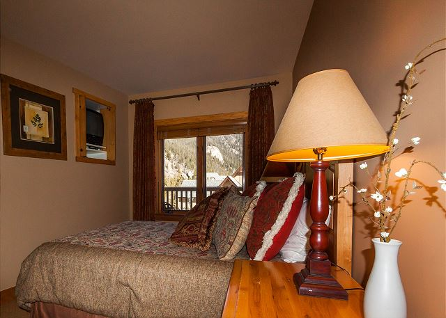 The bedroom features a queen-sized bed, a television and mountain views from the windows.