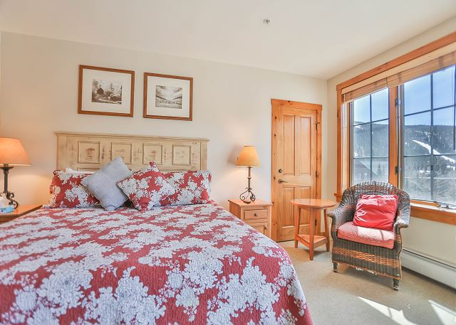 The master bedroom features a king-sized bed, a mounted flat screen TV and its own access to the balcony.