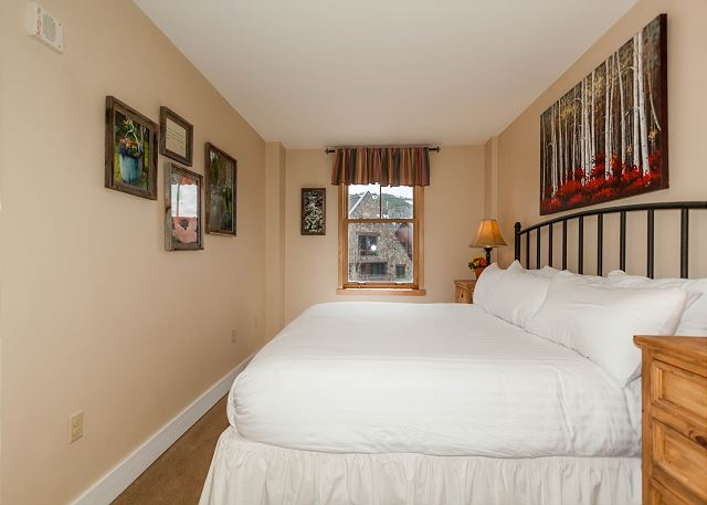 The master bedroom features a king-sized bed with Ivory White bedding.