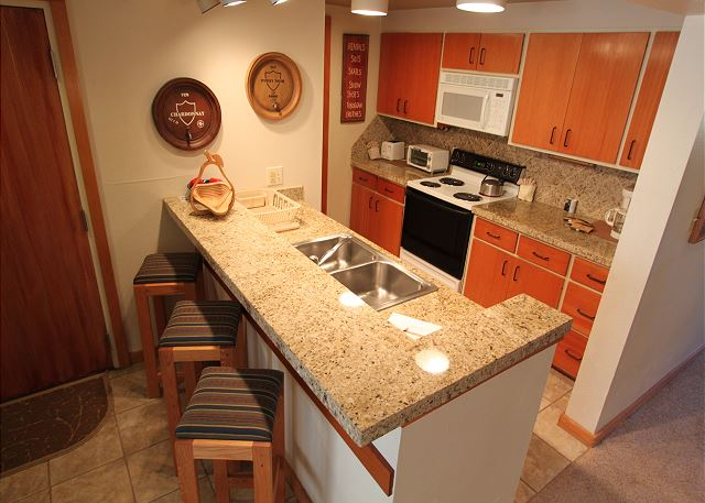 The kitchen features granite countertops and a breakfast bar with seating.