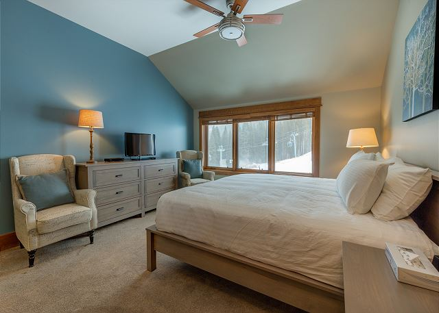 The second master bedroom features a king-sized bed with Ivory White Bedding, a flat screen TV and beautiful ski slope views.