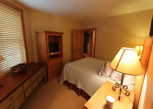 The second master bedroom features a queen-sized bed, flat screen TV and an en suite bathroom.