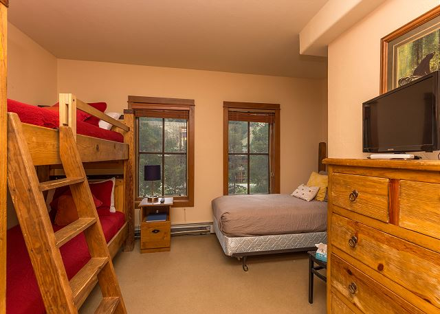 The second bedroom features a twin-sized bed, a twin-sized bunk bed and a flat screen TV.