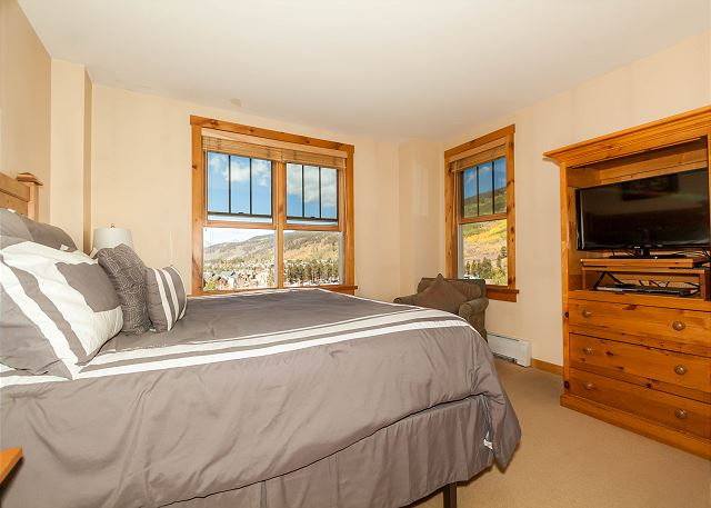 The master bedroom features a king-sized bed and flat screen TV. There's also a dedicated workspace near the door.