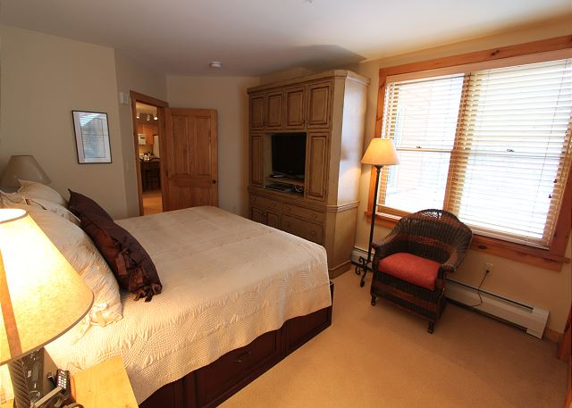 The first master bedroom features a king-sized bed, flat screen TV and an en suite bathroom.