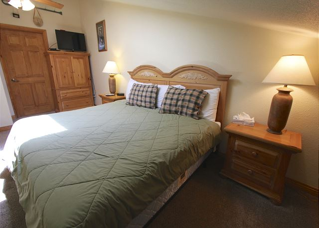Master bedroom features a king-sized bed, flat screen TV and a skylight.