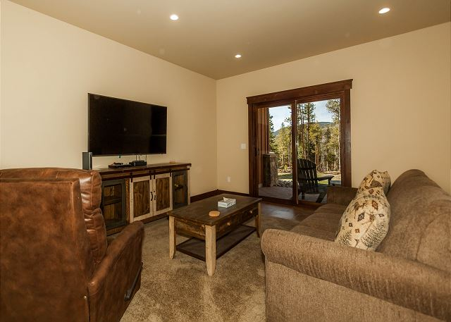 The den downstairs offers a flat screen TV, queen-sized sleeper sofa and walk-out patio.