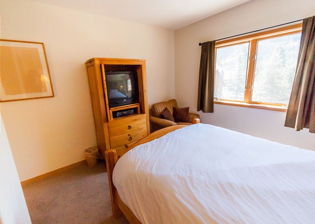 The first guest bedroom features a queen-sized bed with Ivory White Bedding, a television and its own private bathroom.