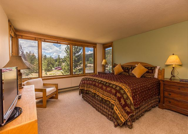 The master bedroom features a king-sized bed, a flat screen TV and beautiful views through the picture frame windows.