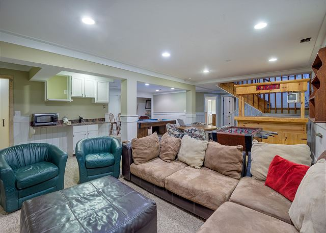 The basement offers comfortable seating for watching movies on the flat screen TV.