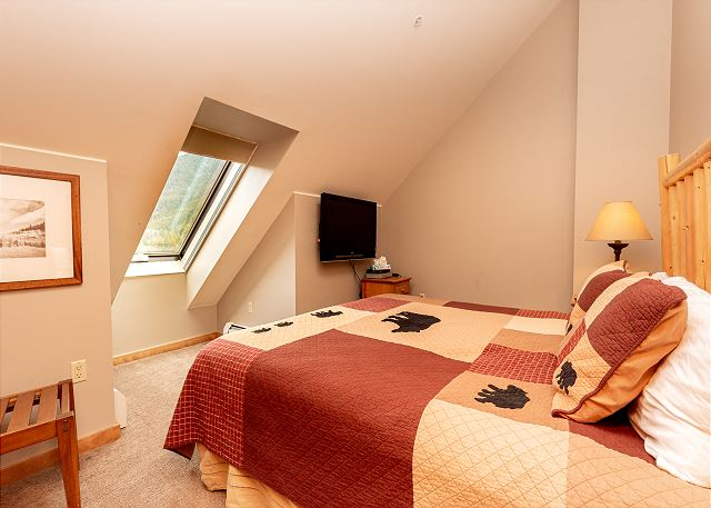 The guest bedroom features a king-sized bed and a mounted flat screen TV.
