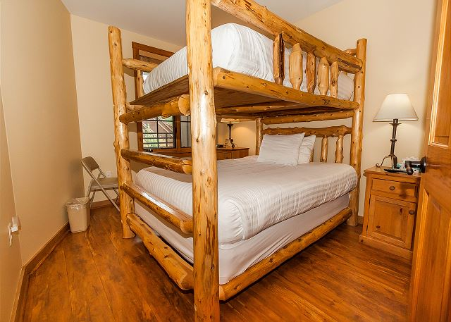 The guest bedroom features a queen-sized bunk bed with Ivory White Bedding.