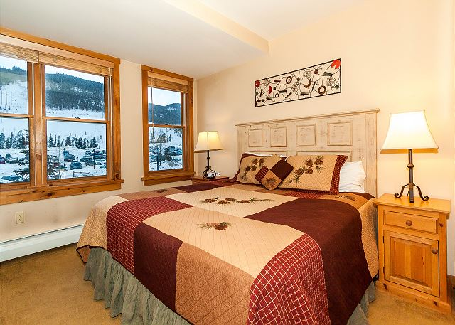 The master bedroom features a king-sized bed, a flat screen TV and mountain views.