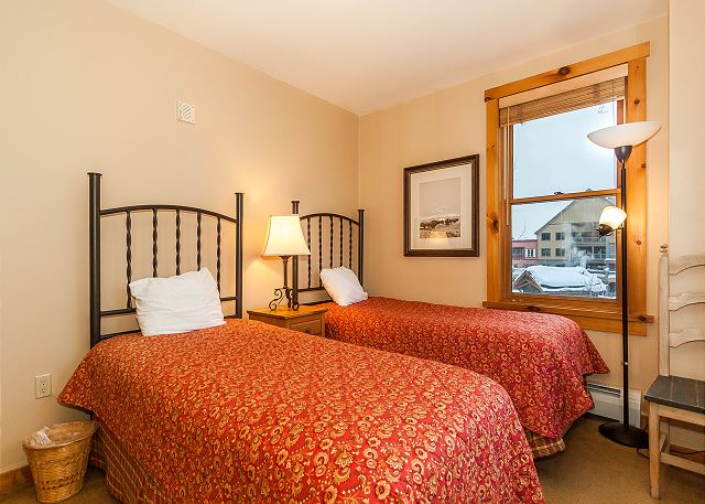 The guest bedroom features two twin-sized beds and mountain views.