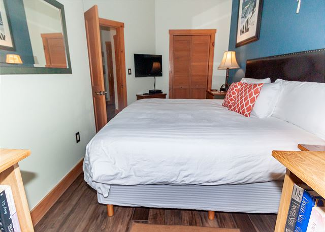 The bedroom features a king-sized bed and a mounted flat screen TV.