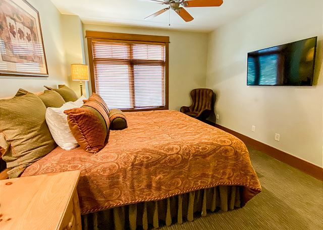 The master bedroom features a king-sized bed, a flat screen TV and slope views.