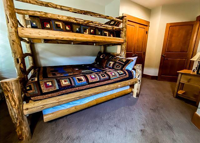 The guest bedroom features a twin-over-queen bunk bed with a twin trundle.