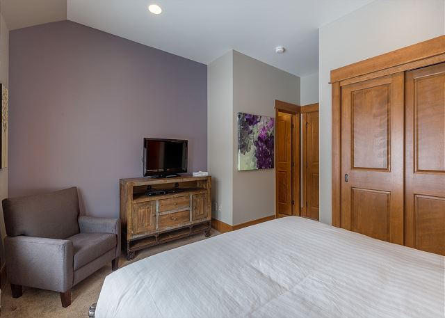 The first guest bedroom features a queen-sized bed with Ivory White Bedding, a flat screen TV and beautiful slope views.
