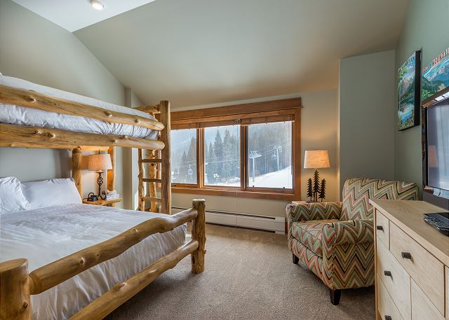 The second guest bedroom has a bunk bed with a full-sized bed on the bottom and a twin-sized bed on the top, both with Ivory White Bedding. There's also a flat screen TV.