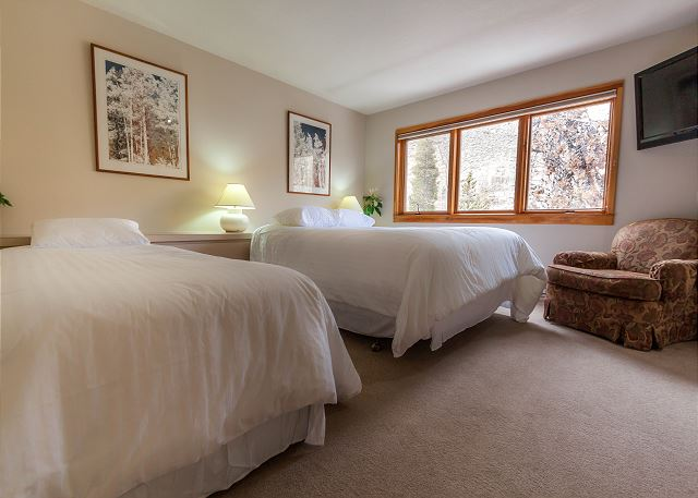 The guest bedroom features a queen-sized bed and a twin-sized bed, both with Ivory White Bedding and a mounted flat screen TV. There is also a twin-sized mattress that can be pulled out for an additional sleeping arrangement.
