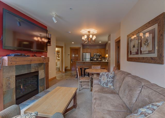 The living area features a mounted flat screen TV above a gas fireplace and a queen-sized sleeper sofa.