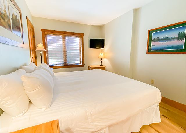 The master bedroom features a king-sized bed and a mounted flat screen TV.
