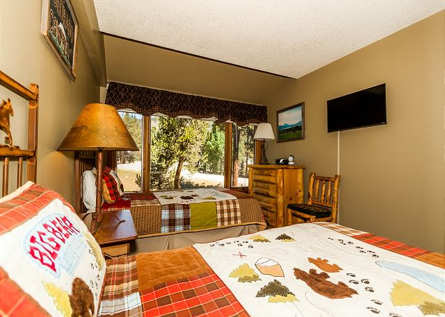 The third guest bedroom is downstairs and features two twin-sized beds and a mounted flat screen TV.