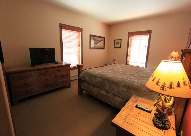 The master bedroom features a king-sized bed and flat screen TV.