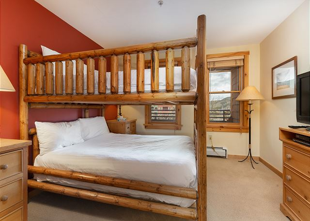 The guest bedroom features a queen-sized bunk bed with Ivory White Bedding and a flat screen TV.
