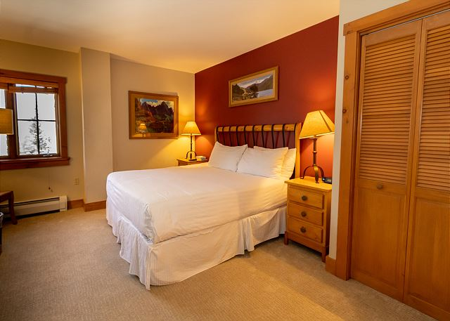 The second master bedroom features a king-sized bed with Ivory White Bedding and a flat screen TV.
