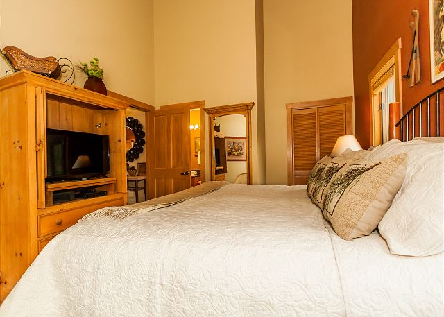 The first master bedroom features a king-sized bed, a flat screen TV and village views.