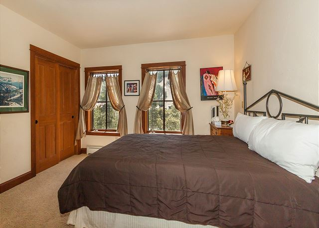 The bedroom features a queen-sized bed, a flat screen TV and beautiful slope views from the windows.