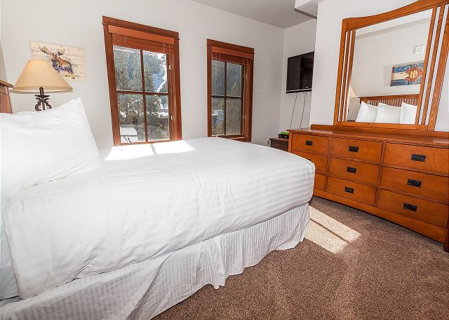 The first guest bedroom features a queen-sized bed on our Ivory White Bedding program and a mounted flat screen TV.