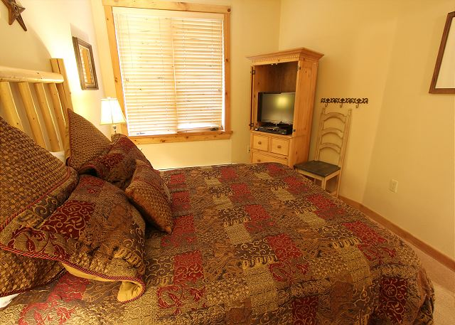 Guest bedroom features a queen-sized bed and a flat screen TV.
