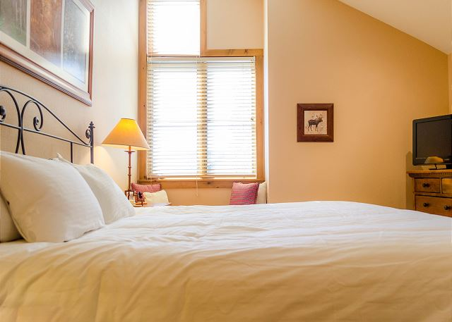 The master bedroom features Ivory White Bedding on a king-sized bed and a flat screen TV.