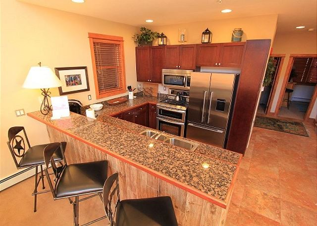 Full-sized kitchen with granite countertops and stainless steel appliances.