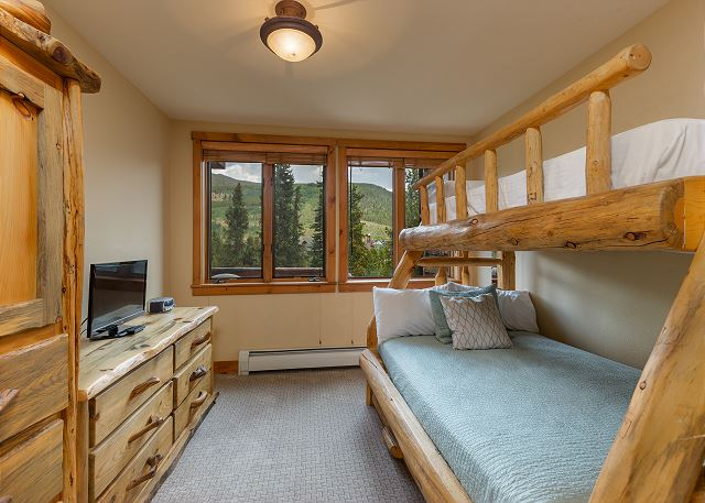 The guest bedroom features a twin-over-full bunk bed with a twin trundle. It also has a flat screen TV and an en suite bathroom.
