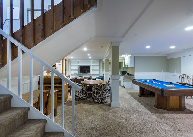 The basement is a recreation room featuring a large flat screen TV, a comfortable seating area, a pool table, a small bar, a game table, a sauna and two guest bedrooms.