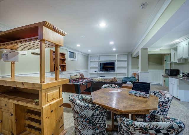 The basement offers a small bar and a game table.