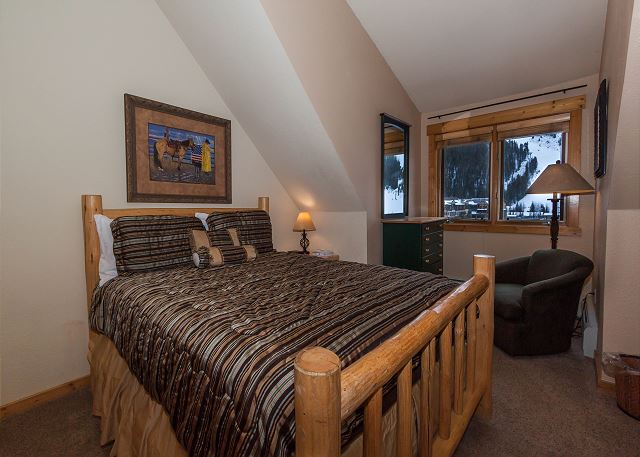 The first guest bedroom features a queen-sized bed and a mounted flat screen TV.