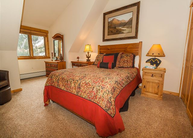 The master bedroom features a queen-sized bed, vaulted ceilings and a mounted flat screen TV.