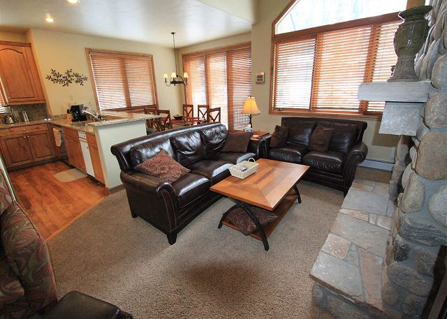 The living area features a large flat screen TV and a beautiful stone gas fireplace.