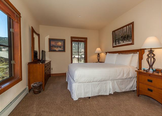 The master bedroom features a queen-sized bed with Ivory White Bedding and a flat screen TV.