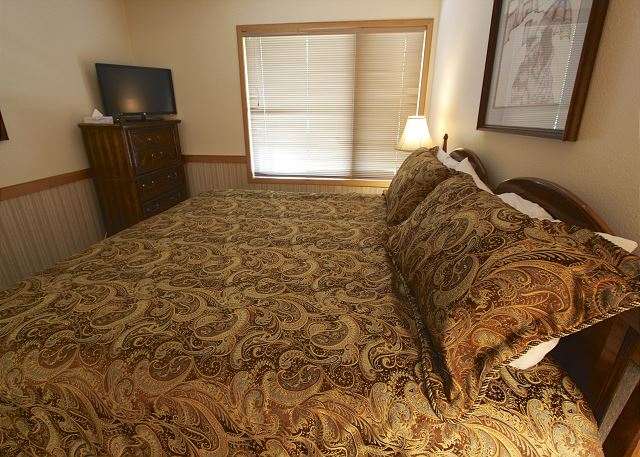 The master bedroom features a king-sized bed and a flat screen TV.