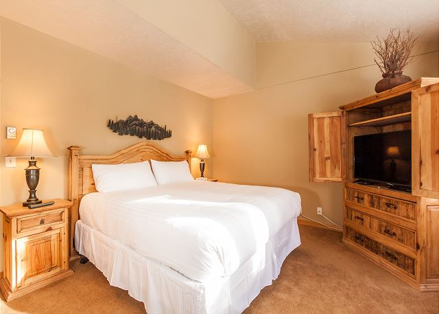 The master bedroom features a king-sized bed with Ivory White Bedding, a flat screen TV and beautiful views.