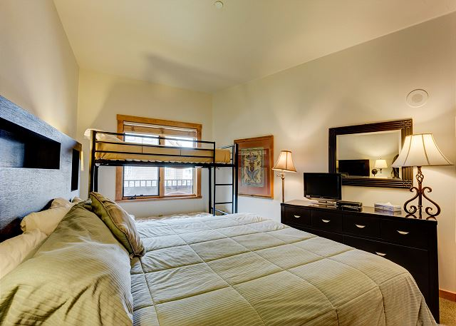 The bedroom features a king-sized bed and a twin-sized bunk bed. There is also a flat screen TV.