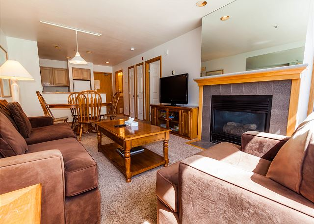 The living area features a flat screen TV, gas fireplace and a queen-sized sleeper sofa.